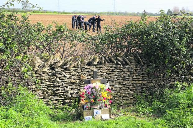 Swindon Advertiser: Police in the field at Eastleach yesterday. In the foreground is the memorial to Becky Godden-Edwards, close to the site where her remains were found three years ago