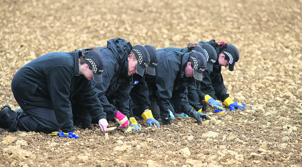 Police officers combing the field at Eastleach on Saturday