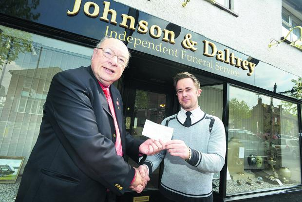 Dick Mattick hands over the cheque to David Daltry for the restoration work on the grave of Sam Allen