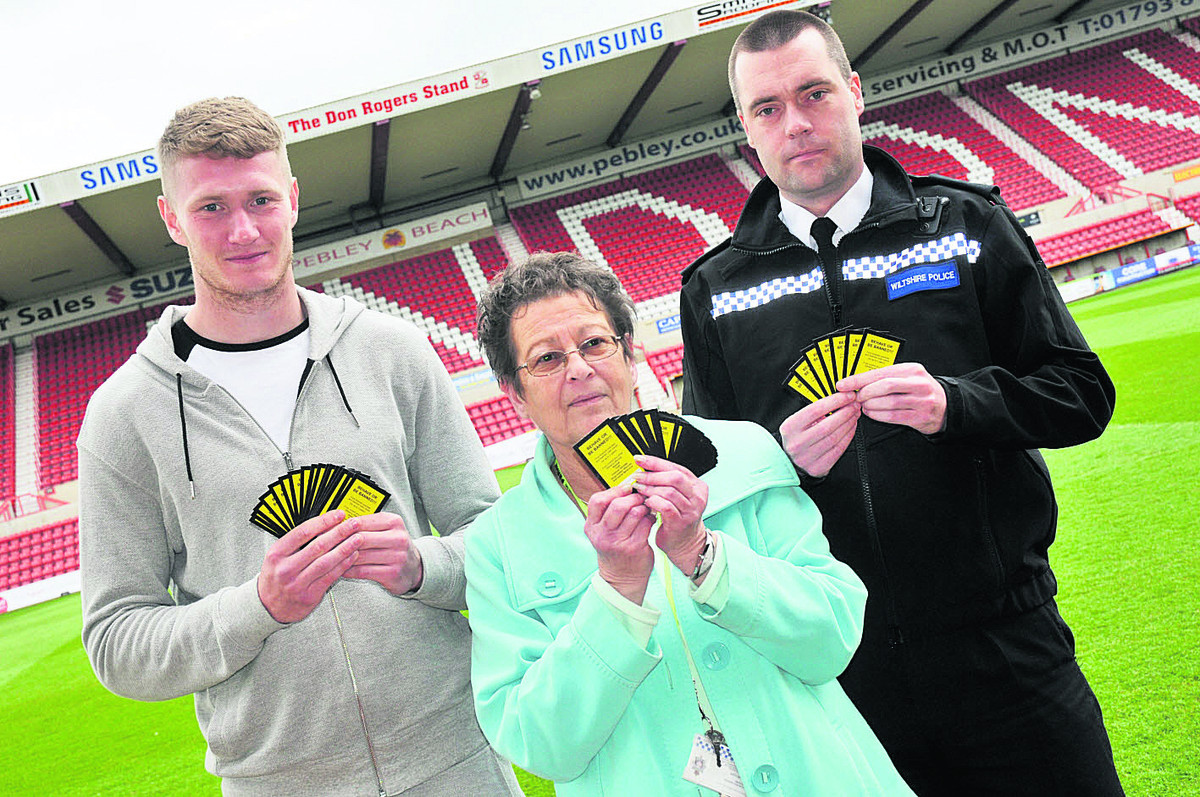 Swindon Town player Michael Smith, Jane Dudley of Swindon CSP and Insp Paul Saunders with the World Cup yellow cards