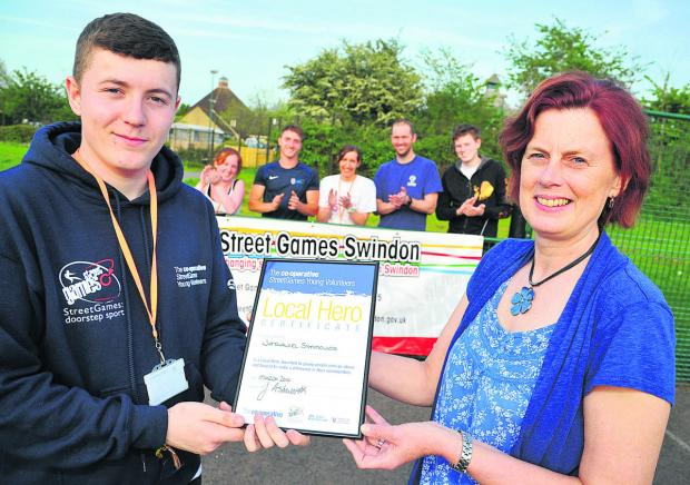 Nathaniel Symonds receives his Local Hero award from Gladys Barr, manager of Swindon Council Leisure Services' outreach sport and physical activity team