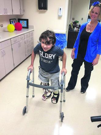 Luca Railton takes his first steps since his life-changing operation seven weeks ago