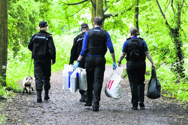 Police carrying evidence away from Lawn Woods in plastic sacks in after the drugs swoop yesterday. Picture: Alex Skennerton