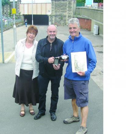 Barry Leighton presents Diane Everett and Andy Binks, of the Swindon Society, with Richard Bullen's mug at the location of the Union Hotel, now part of a car park adjoini