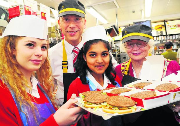 Student Taylor, Paul Booth, the franchisee of McDonalds, student Astria and mayor Teresa Page making burgers at McDonalds, in Great Western Way