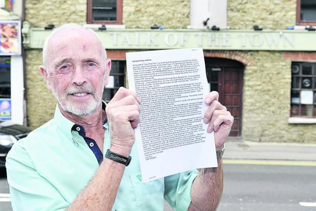 Tony Holmes outside the closed Talk of the Town salon holding his open letter