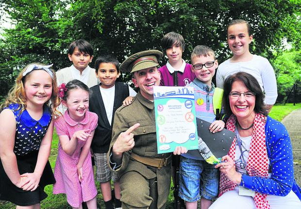 Indy Mark Andrews, third right, receives his award from actor David Cooper and school eco travel  coordinator Avril Brown, surrounded by pupils, from left, Grace, Bethany, Zak, Adam, Ewan and Lauren