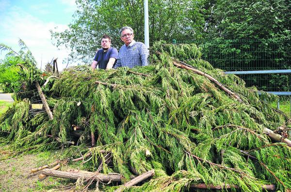 Councillors Neil Heavens and Derique Montaut peer  over the green waste