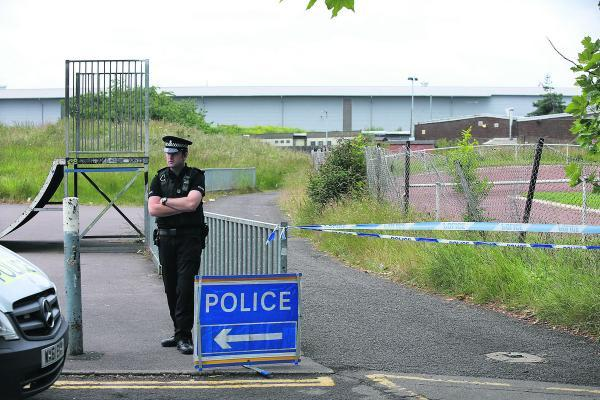 A police officer guards the scene after the discovery of the body of Tom Rogers