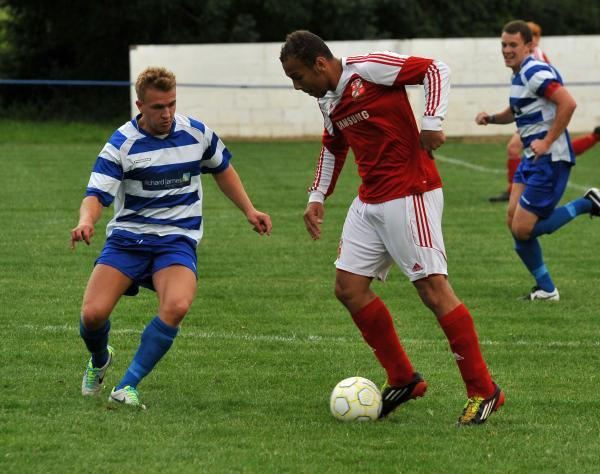 Shrivenham's Gio Wrona and Swindon Town's Josh Cooke in action