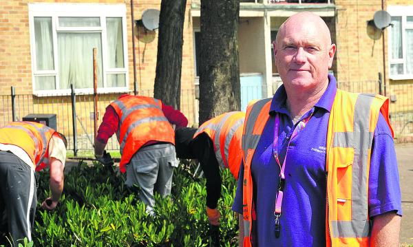 Community Payback Supervisor Doug Mack standing with offenders clearing the area around Sussex Square