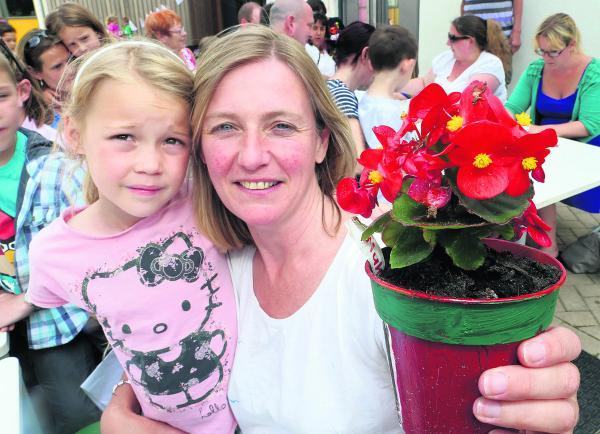 Scarlett, 7, and her mother Kate South with a plant grown by pupils at St Mary' s School, Purton