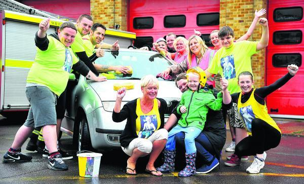 Charlie Allen, front in the green top, at the charity car wash day at Drove fire station