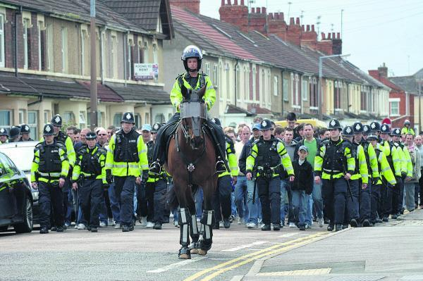 Police escort visiting fans into the County Ground before a match