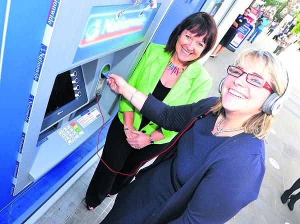 Customer experience directorJenny Groves shows reporter  Liz Mackley how to use Nationwide's new cash machine in Regent Street
