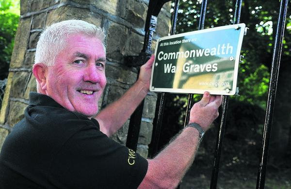 Tony Murray with the repaired Commonwealth War Grave sign at Radnor Street cemetery