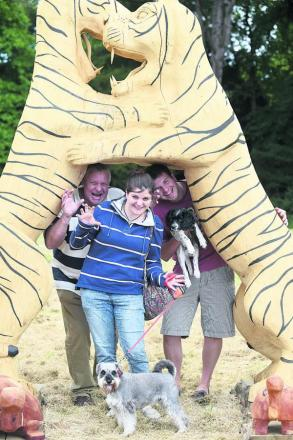 Paul, Amy and Sam Middleton with dogs Bo and Alfie under the two tigers woodcarving by Steve Griffin