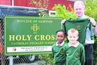 Holy Cross Catholic Primary School which has new uniforms to go with the name. From left, pupils Beatrix and Adam with head teacher Tony McAteer