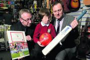Morgan Sharpe who has Goldenhar Syndrome with Alan Holmes, left, and Nathan Jones and the signed memorabilia