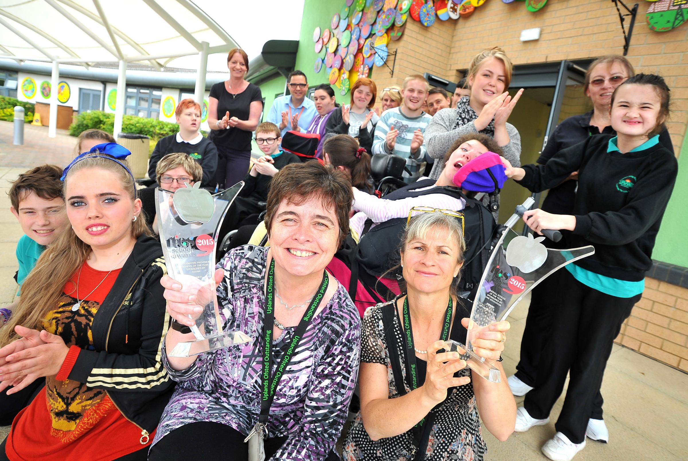 From left, showing off trophies are Uplands School headteacher Deirdre Fitzpatrick and executive headteacher Jackie Smith, with proud school pupils