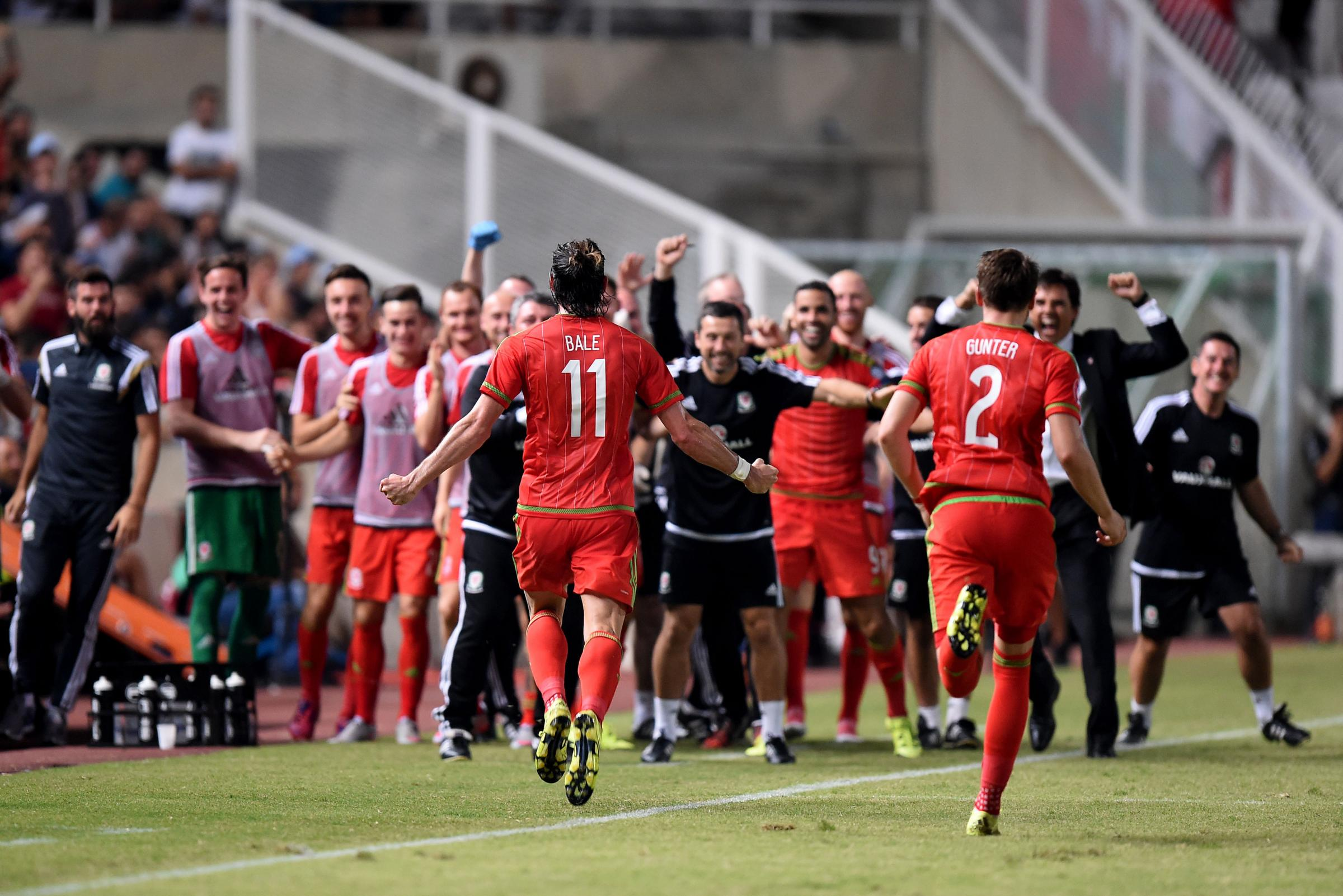 The Wales bench, including Town loan man Jordan Williams, celebrates Gareth Bale's winner in Cyprus