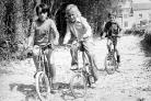 Children ride their bikes in a dried up river bed in 1976