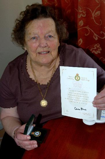 Former Land Girl Iris Sturgeon with her badge and certificate from the Prime Minister