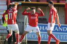 Nicky Ajose (centre) leads the celebrations after Swindon Town's winning goal against Millwall on Saturday with scorer Conor Thomas (right) and James Brophy