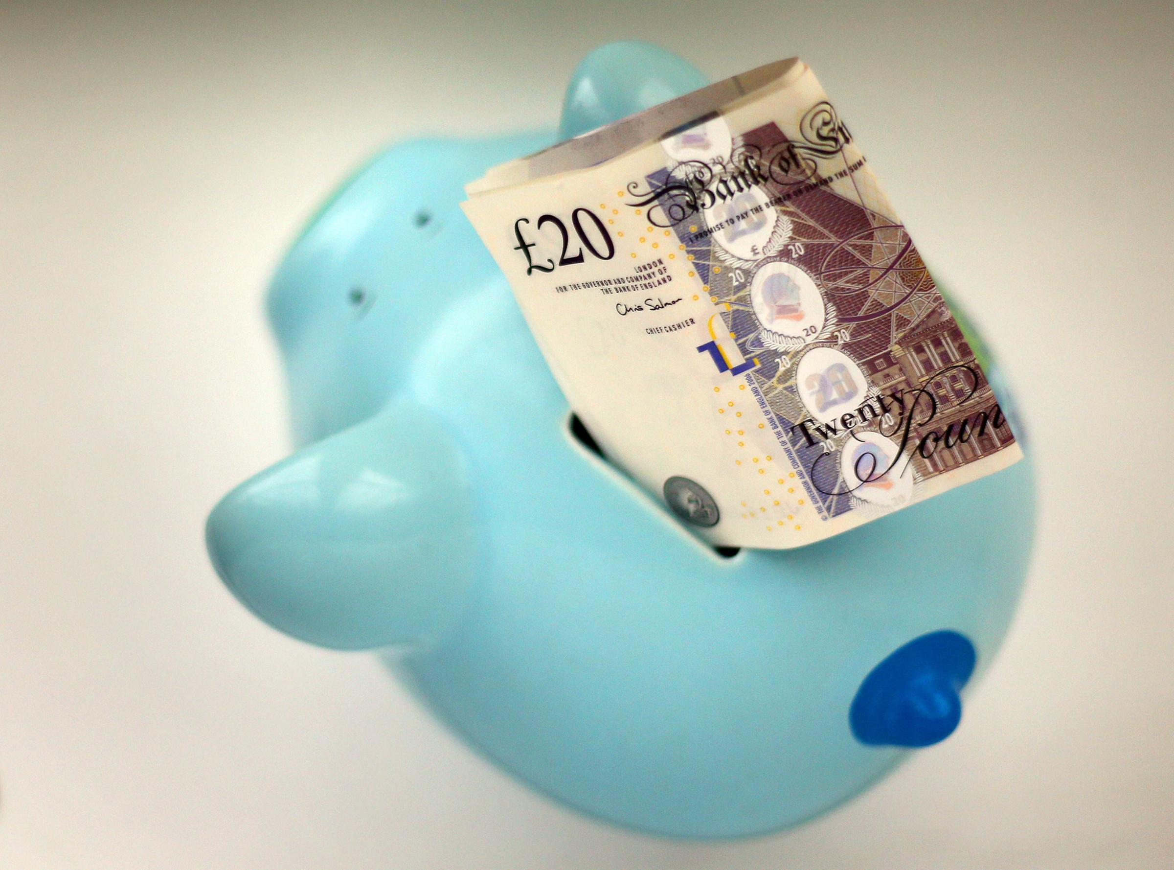 File photo dated 06/01/15 of money in a piggy bank, as families working full time on the national living wage are 13% or £59 a week short of the amount needed to provide their children with a minimum standard of living, according to a new report. PRESS A