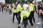 Police hold a man during the second and final day of the Notting Hill Carnival in west London.