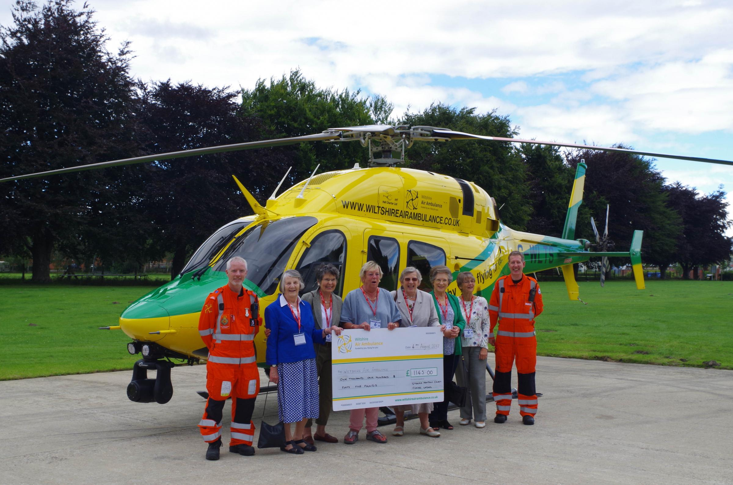 The Flower Ladies of St Mary's Church, Steeple Ashton present the cheque to Wiltshire Air Ambulance staff