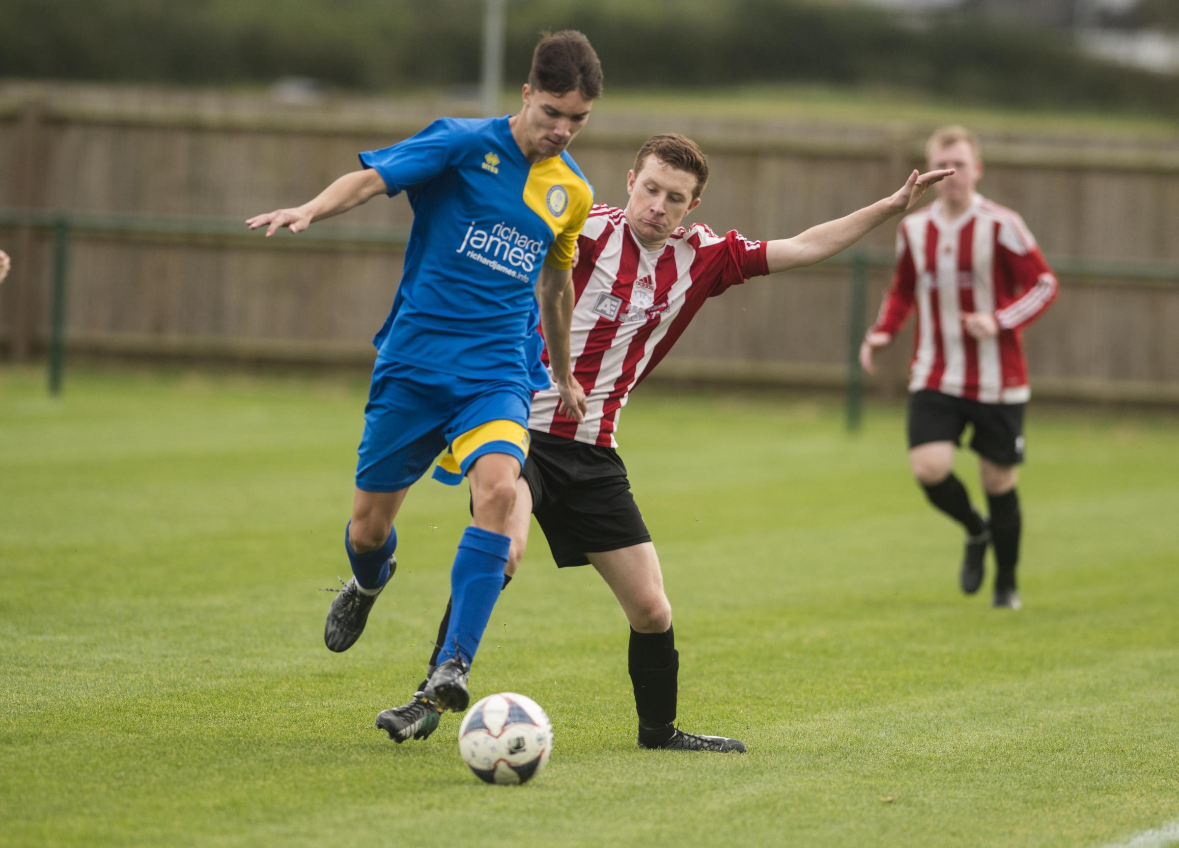 Royal Wootton Bassett Development's Josh Harris (blue) is challenged by Devizes Town Reserves' Jamie Hall during Saturday's clash Picture: CLARE GREEN