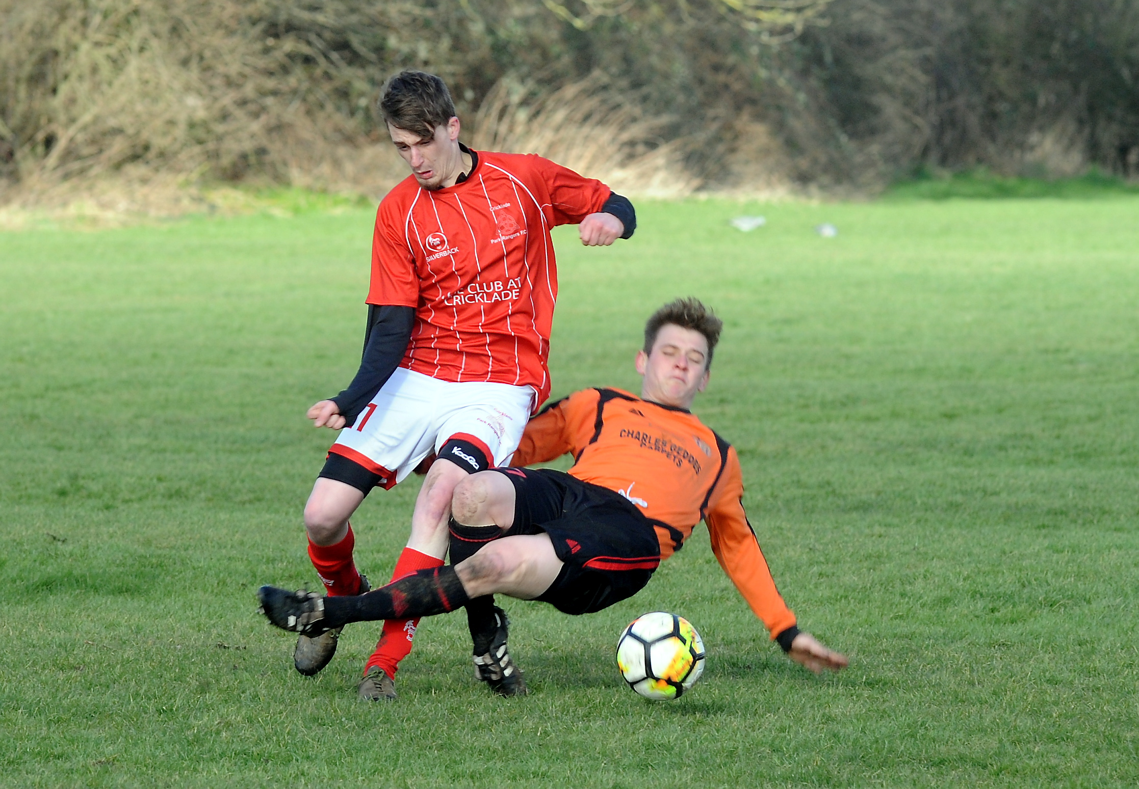 Charles Geddes player Lee Toomey (orange) gets a meaty challenge in during his side's Bunny Uzzell Memorial Shield clash against Cricklade Park Rangers (Pictures: PAUL NICHOLLS)