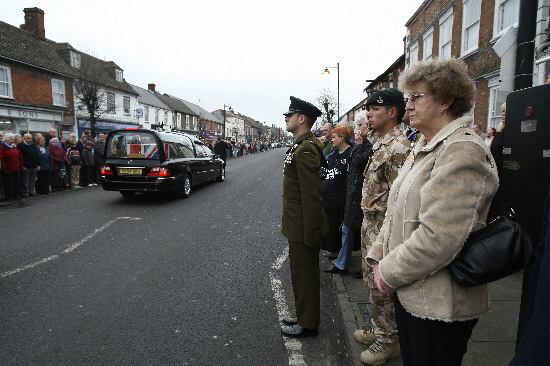 Richard Robinson, second right in camoflague, pays his respects as colleague Stuart Nash is repatriated through Wootton Bassett