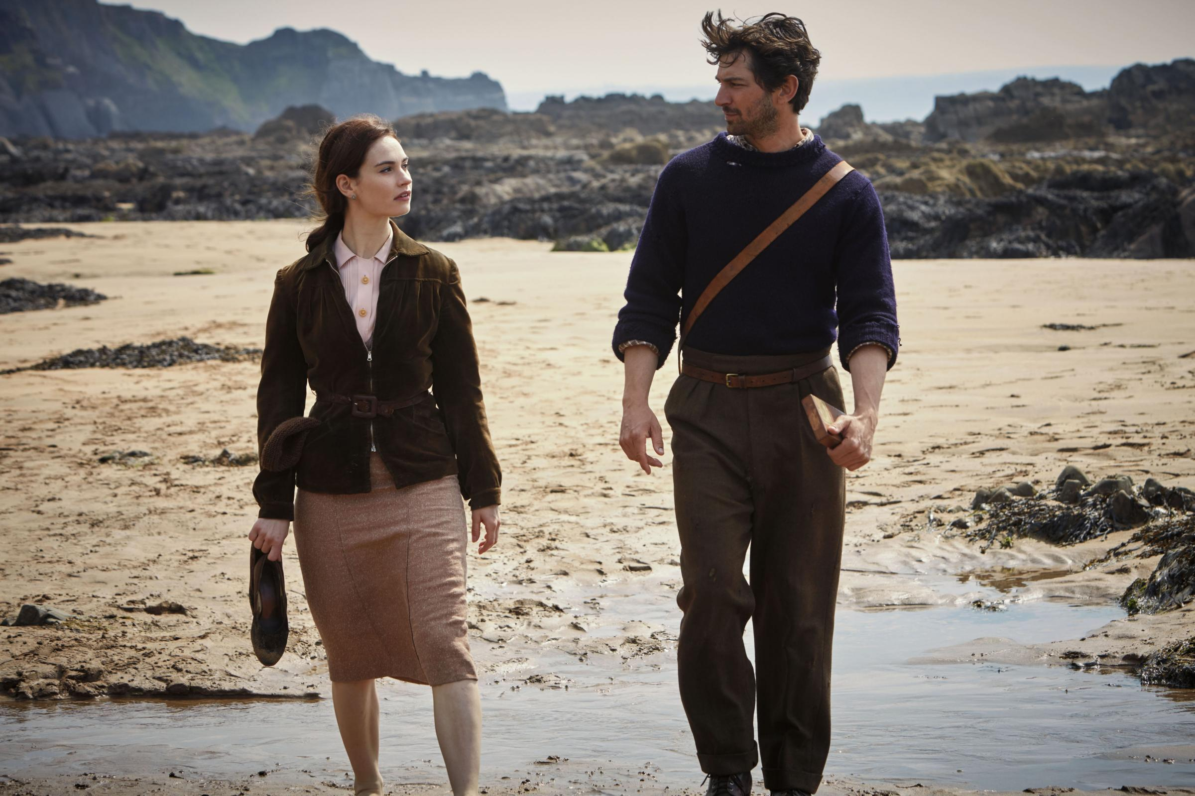 Lily James as Juliet Ashton and Michiel Huisman as Dawsey Adams take a stroll on the beach in The Guernsey Literary And Potato Peel Pie Society