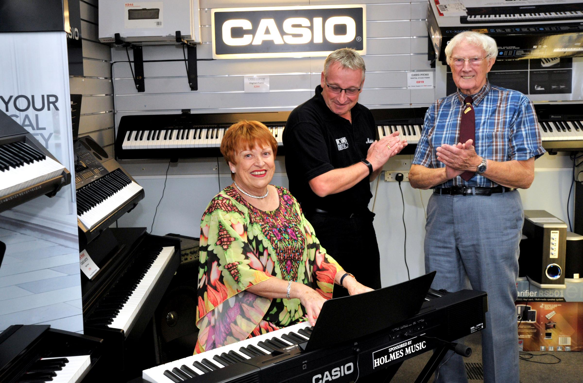 Trying out the new piano is Sheila Harrod, from Kentwood Show Choir watched by Alan and John Holmes from Holmes Music Picture: Dave Cox