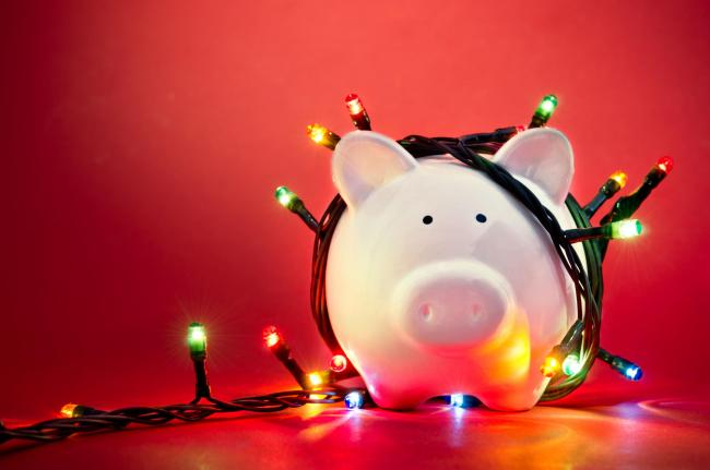 Piggy bank wrapped in Christmas string lights.