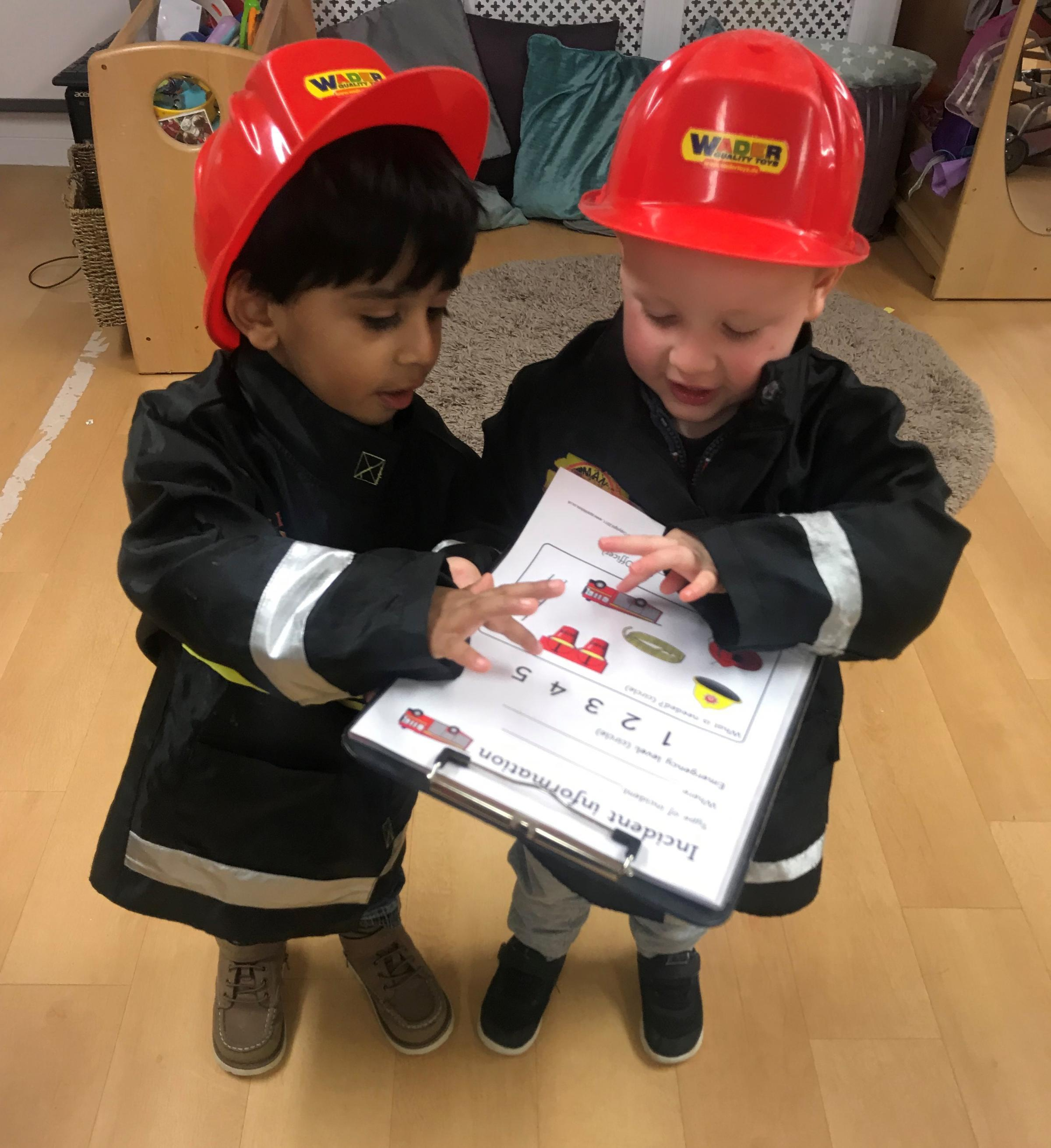 Pre-school children at Windmill Hill Day nursery trying on being a firefighter for size