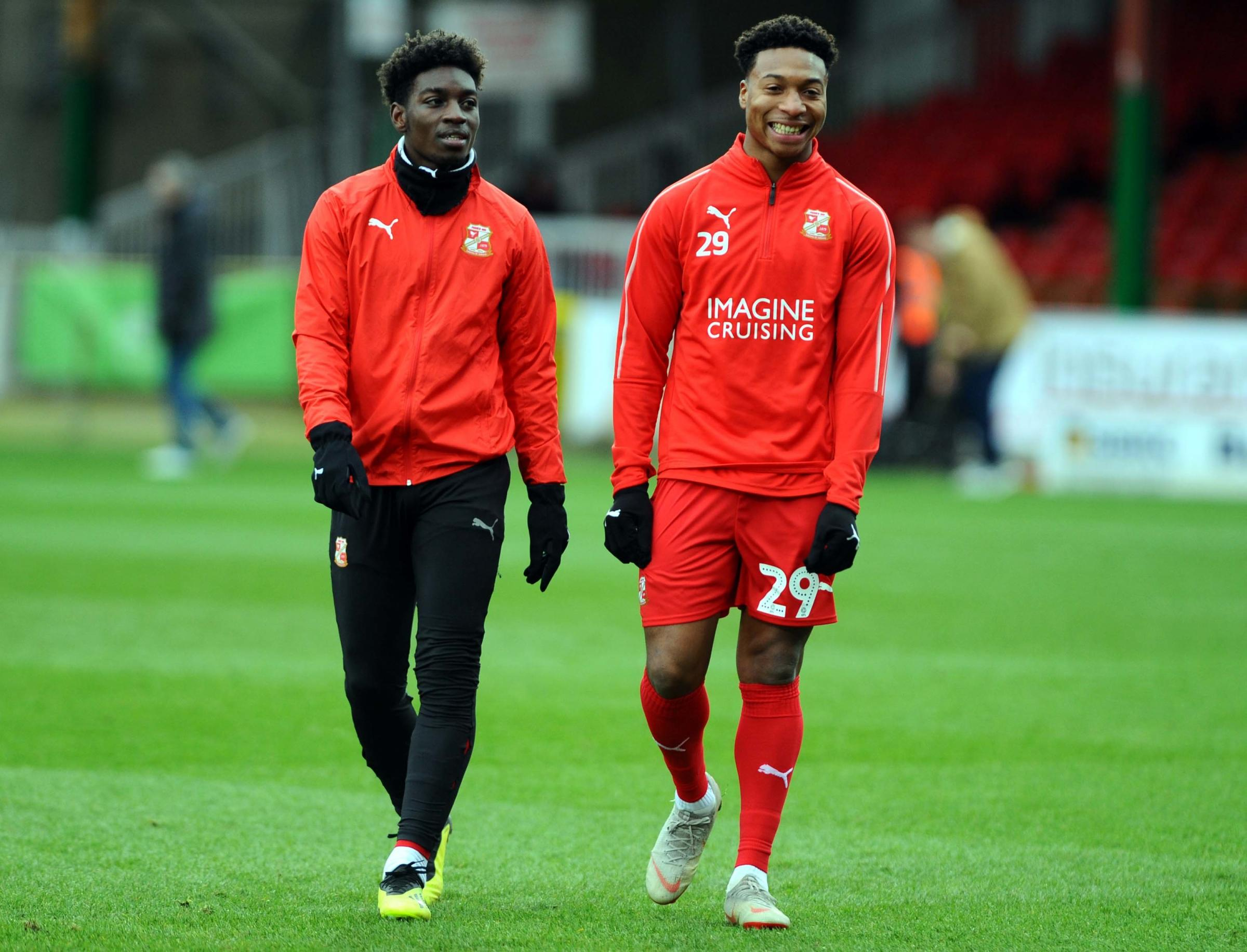 Ali Koiki (right) shares a joke with team-mate Jermaine McGlashan during a warm-up ahead of a recent Swindon Town game