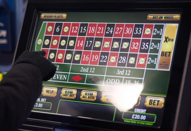 File photo dated 12/01/13 of a someone using a gambling machine. Fixed-odds betting terminals (FOBTs) cost taxpayers as much as £210 million a year due to the impact on frontline services, according to research. PRESS ASSOCIATION Photo. Issue