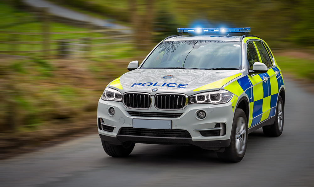 Whitby, United Kingdom - May 1, 2015: A police vehicle speeds to an emergency on a country road..