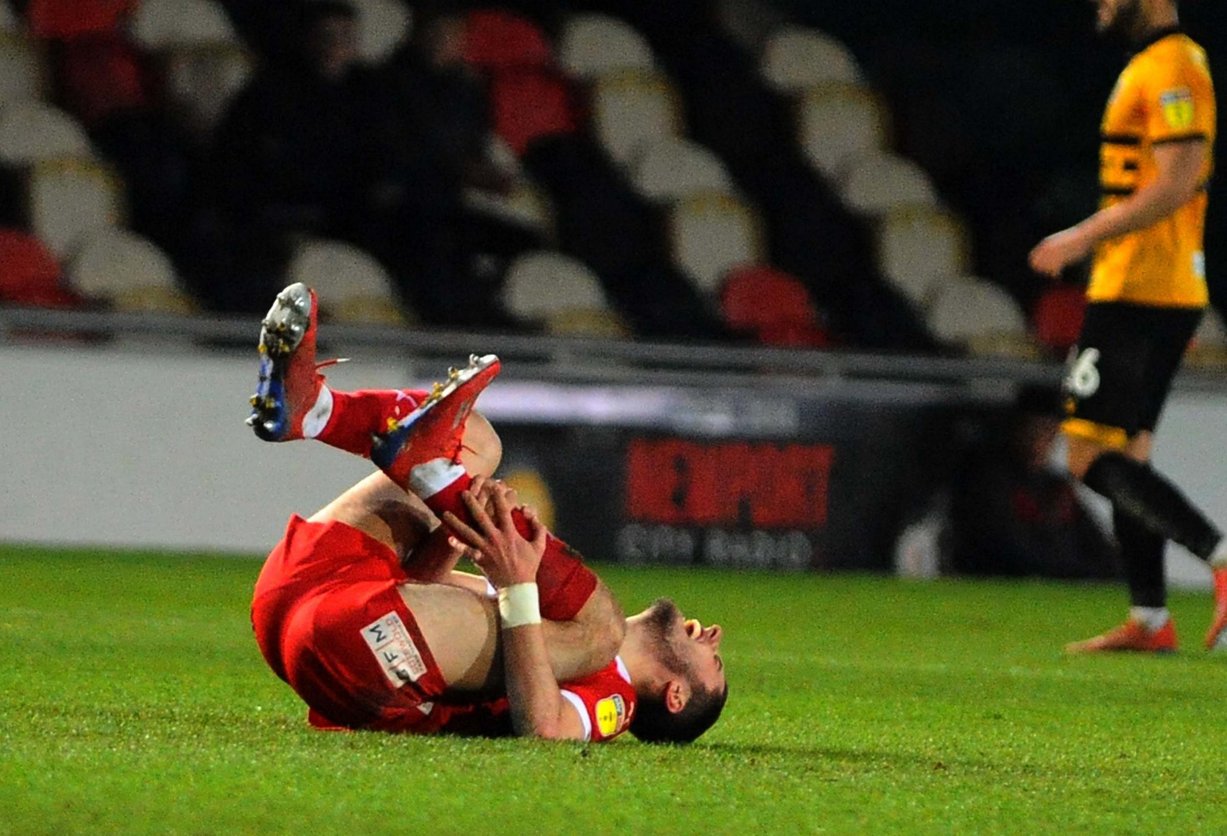 Swindon Town midfielder Canice Carroll holds his leg in pain during Tuesday night's 0-0 draw away at Newport County - an injury that forced him off the pitch in the closing stages Picture: DAVE EVANS