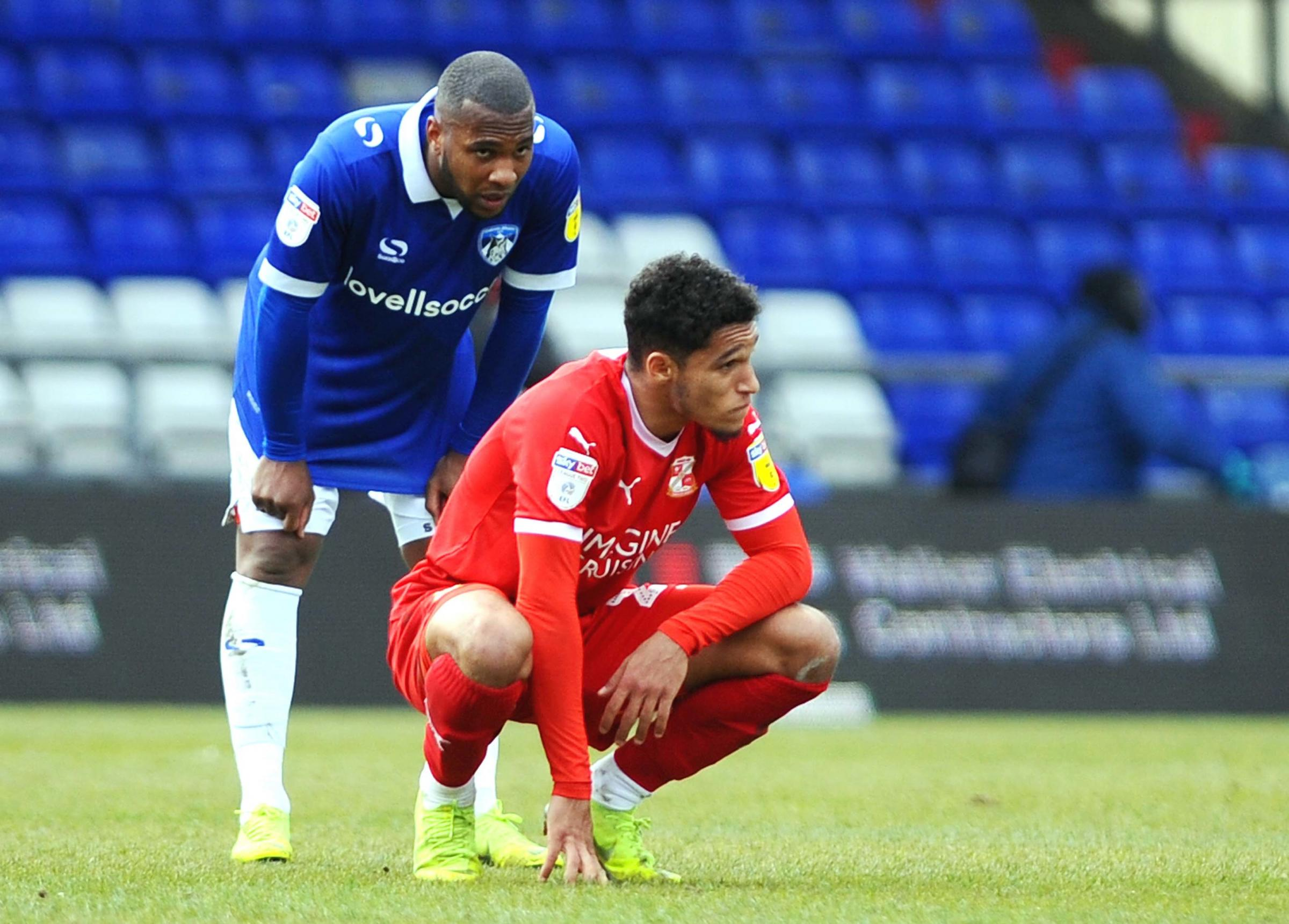 Swindon Town's Kyle Knoyle (red) and Oldham Athletic's Gevaro Nepomuceno cannot hide their disappointment following the full-time whistle of the 2-2 draw between the two teams at Bounday Park on Saturday - a result that left both with an uphil