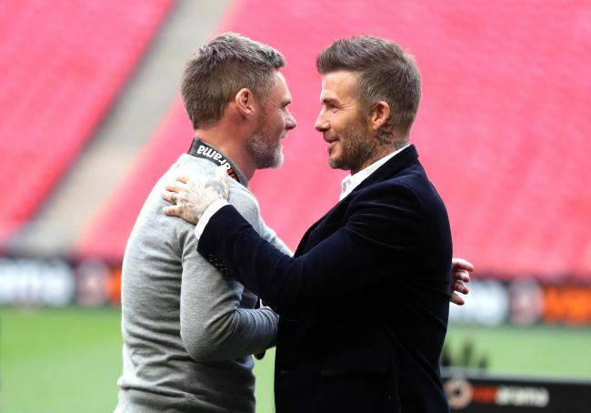 Salford City co-owner David Beckham embraces manager Graham Alexander after winning the Vanarama National League Play-off Final at Wembley Stadium, London.