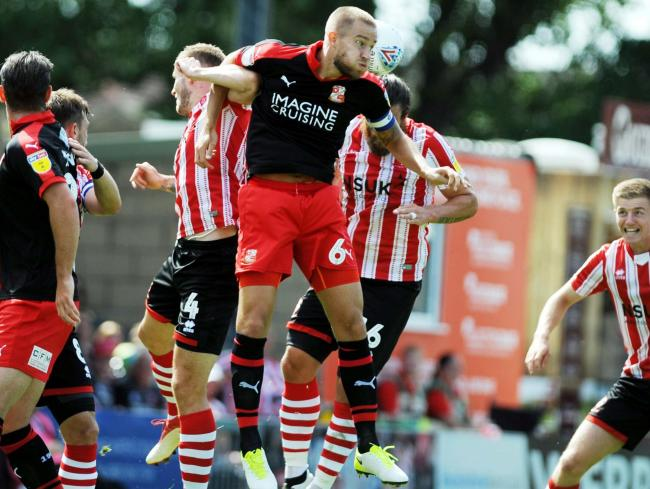 Olly Lancashire beats two Lincoln players to head clear for Town at Sincil Bank on Saturday. Picture: DAVE EVANS